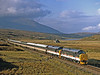 37251 and 37152 have reached the top of the climb up Glen Carron from Strathcarron and are now at Luib on the watershed before dropping down past Loch a Chuillin to Garve with their  Monarch of the Glen Luxury Land Cruise on 3rd October 1993.