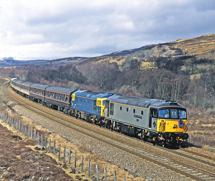 33116 and 33109 are unusual visitors to the HML as they roll down from Drumochter to Blair Athol past falls of Clunes with a long distance charter on 1st April 1995.