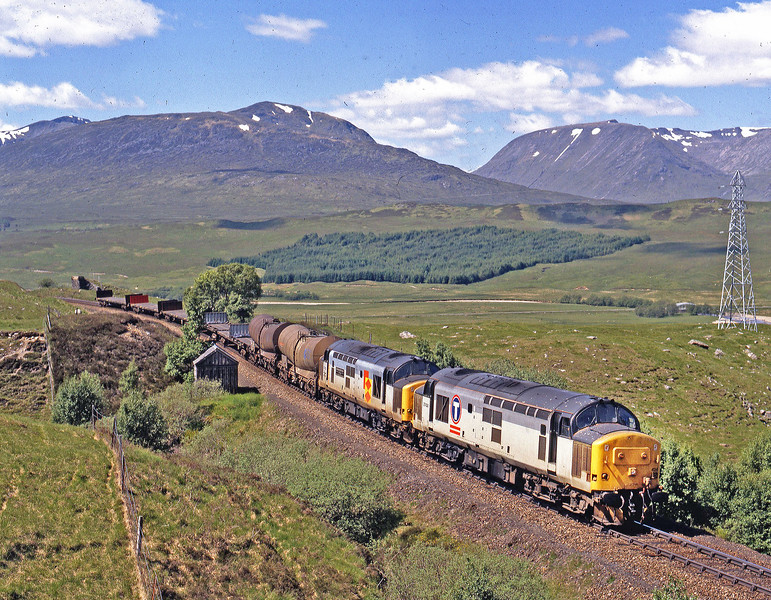 Running in the more favourable earlier path, 37425 & 37423 have an easy job on the morning Mossend to Fort William Enterprise with only 2 loaded china clay tanks and a few flats as they shut off for the PSR over the small viaduct at Achallader on 14th June 1995.