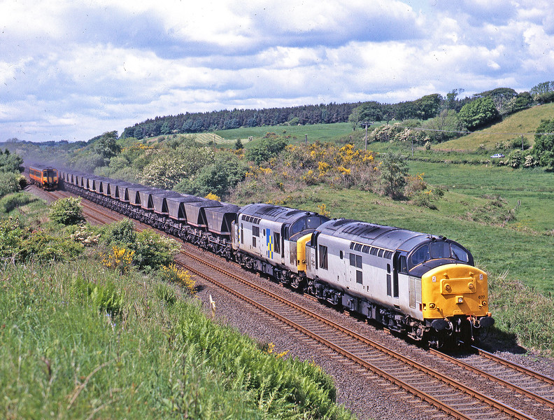 "The Strathclyde liveried Newcastle to Glasgow DMU is almost enveloped in the ""blow-off"" from the train of Ayrshire coal on its way to the Aire Valley, seen here racing across the Solway plain at Cummertrees on 7th June 1995. 37677 & 37686."