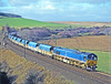When my friends in the EWS coal planning office advised me that NP were going to run a trial load from Hunterston to Drax using one of their attractively liveried 59/2s pulling their well maintained hoppers I felt it was an opportunity that was too good to miss. The forecast on the day gave no hope of sun but I set off on the 80 miles to Houndwood where the sun, if out, would be at the perfect angle. There were some very small breaks in the cloud and I trudged up to the viewpoint feeling that my luck was out again. However at about the time it should be leaving Grantshouse loop, 1 mile to the north, a miniscule break appeared in the cloud cover and almost immediately the 59 came into sight. I did not dare look behind at the sun as I did not want to be blinded when taking the shot. The sun went in before the last wagon had passed and that was it for the day. Farcically the train ran as 6Z36 as far as Berwick upon Tweed and then 4Z36 south from there. The Scottish Region CE restricted it to 60mph but his ER counterpart was happy for it to run at 75. Although this trial was deemed successful it never happened again. 12.30 on 26th Feb 1998. 59201 PRIDE OF YORK.