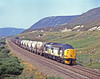 Heavywerigh 37708 has just come over Drunochter Summit with the daily Inverness to Mossend Enterprise and is now rolling downhill towards Blair Atholl on 26th July 1990. This loco worked this diagram for what seemed months during 1990.