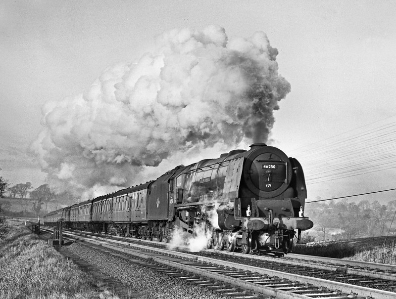 46250 CITY OF LICHFIELD. On the penultimate day of 1963 I arrived at Upperby to find the stand-by being scrambled as the driver of the up Royal Scot had wired forward for a fresh engine at Carlisle, having decided to give up on his struggling Class 40. There were always a few headboards lying in the stores at Upperby and I raced round to find a ROYAL SCOT but to no avail. There were some that never came anywhere near Carlisle such as the MERSEYSIDE EXPRESS and the EMERALD ISLE EXPRESS but no ROYAL SCOT. The Upperby crew were to work forward as the second man on the diesel was not a fireman. There was no doubt that they were going to make up the lost time and here they are flat out on the climb away from Carlisle at Wreay South on 30th December 1963. This was probably the last steam working of this flagship train.