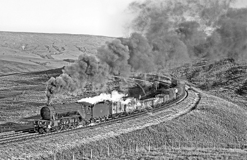 On 17th July 1965 – 51 years ago! – the syncopated exhaust of V2 60846 is reverberating round the border hills as it approaches Riccarton Jct powering the 18.xx Carlisle Yard to Craiginches – a train which had been worked by diesel power for at least 3 years. The only normal sounds at this remote location were the occasional cries of moorland birds and the odd noise from sheep. It was a considerable achievement to get the sun here – it must be one of the cloudiest places in GB.