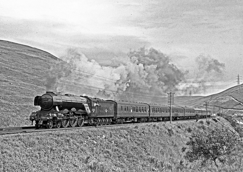 "When I looked at the workings board at Kingmoor on 26th June 1963 I assumed there was a mistake when I saw that a Heaton A3, 60083, was listed to take forward the 10.10 Euston to Perth from Carlisle. I rushed into the shed and there it was, filthy but definitely in steam. The running foreman confirmed that an ""NB engine"" was working the 15.xx 1S63 to Perth. Alan Thompson  was with me and a phone call – no mobiles then- enlisted the help of Stephen Crook and we set off to clean the west side. We just had to find materials where ever we could and managed to find a work platform with very rusty wheels to enable us to reach all of the tender. Reaching the chimney and smokebox top defeated us. We unanimously agreed that Harthope would be the chosen location and so we awaited arrival of the crew who were preparing the loco themselves. It turned out that they were Carstairs men – Driver J Forrest and his fireman who came from Wylam. They were delighted to make some smoke but were concerned that it was not easy with such a loco with a Kylchap blastpipe. In the end they told me later that they resorted to the pricker and there was just enough smoke. Their enthusiasm is obvious – great enginemen."