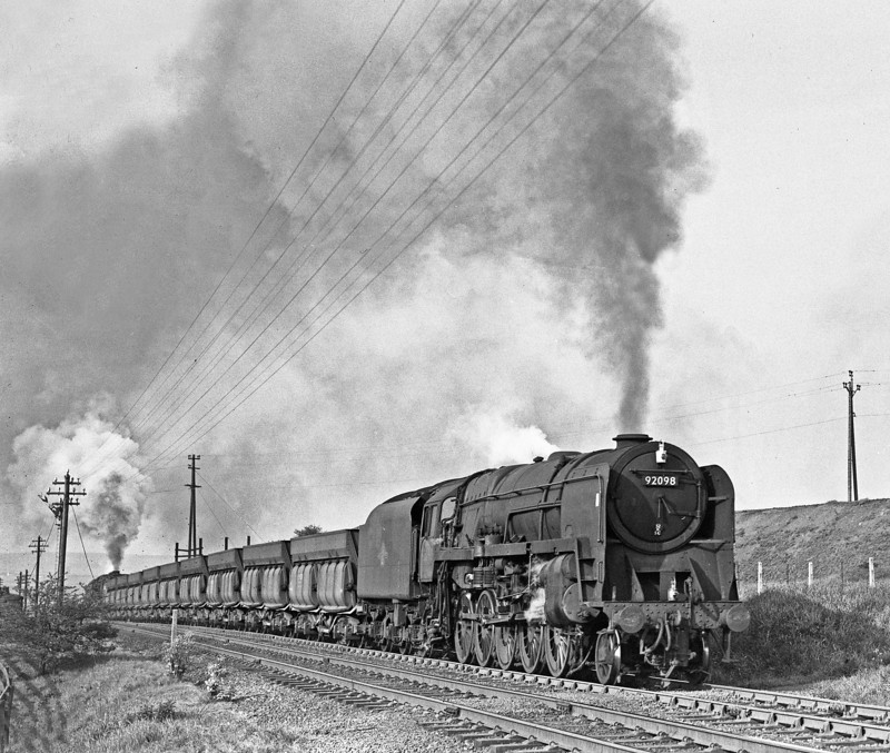 92098 West Stanley on a Tyne Dock - Consett Ore train. Maximum effort is required by these 2 9fs to get their Tyne Dock to Consett train of iron ore up a stretch of 1 in 35 at West Stanley. The change of gradient to a more gentle 1 in 60 is clearly discernable. August 1964