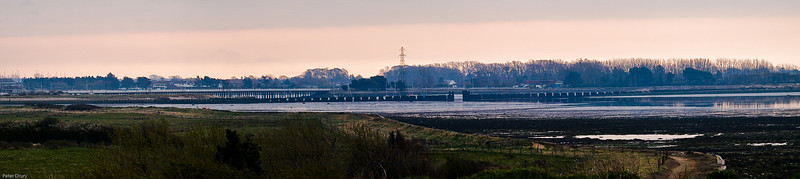 Hayling Island Bridge across Langstone Harbour<br /> This photo was taken from Southmoor on the Langstone Harbour Coastline. Langstone is at the extreme left of the image with the only crossing to the island being the road bridge in the distance. A railway line used to run from Havant station to Hayling Island and crossed the sea in front of the road bridge. The dark piers you can see are all that remain of the wooden viaduct.