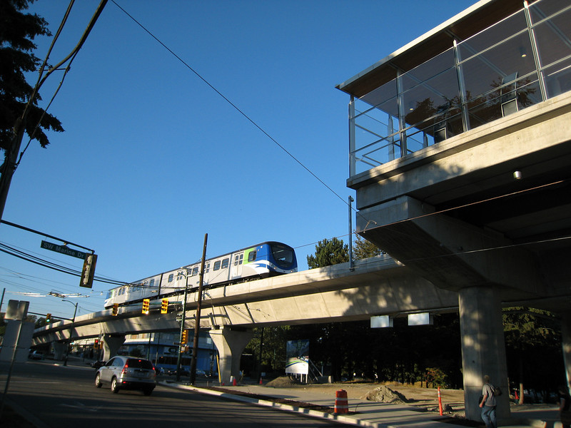 A train arrives at Marine Drive Station, the only elevated Canada Line station in the City of Vancouver.  The line plunges below ground just after crossing Marine Drive, on the left side of this picture.