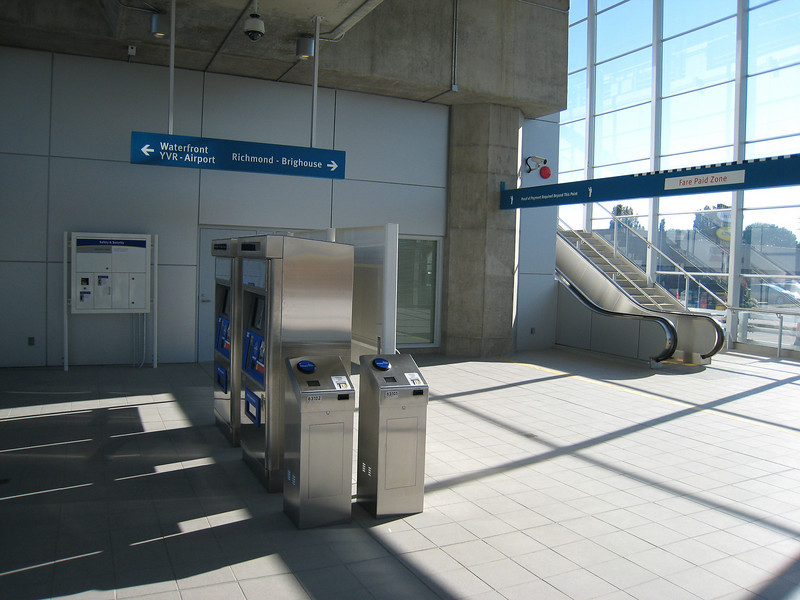 The station concourse at Aberdeen Station is at ground level.  Each elevated station has a similar layout: passengers enter directly beneath the guideway and then ascend escalators to the left or right depending which direction they want to travel.  Unfortunately, the sign visible at upper-right is the only sign indicating the direction of travel until passengers reach the platform level.  In the first week, this led to a fair bit of passenger confusion.