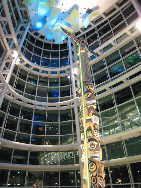 Another view of the totem pole in the Link Building at Vancouver International Airport.  The overhead bridge to the Canada Line station is visible outside the window.