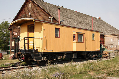 Unmarked wood bay window caboose next to what appears to be an old railroad building in Bozeman, MT. Both are adjacent to the old NP passenger depot. It is reported to be the Butte Anaconda & Pacific #12.