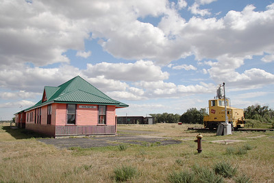 Milwaukee Road depot at Harlowton, MT with shop switcher #3800 on display. Part of the shop buildings are visible in the background.