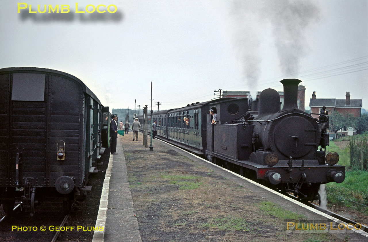 """Trains cross at Havenstreet station - on the right is O2 No. W33 """"Bembridge"""" which had arrived first with the 16:34 train from Ryde Pier Head to Cowes. On the left is the 16:24 train from Cowes having arrived soon after with W28 """"Ashey"""" in charge. A busy scene ensues prior to both trains departing, the station then returning to its slumbers. Friday 4th September 1964. Similar scenes can be witnessed here once again as it is the headquarters of the Isle of Wight Steam Railway. Slide No. 1029."""