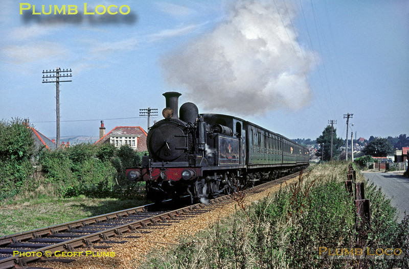 "O2 0-4-4T No. W14 ""Fishbourne"" is heading south between Sandown and Shanklin with the 10:28 train from Ryde Pier Head to Ventnor on Wednesday 2nd September 1964. This is now the location of Lake station. Slide No. 1001."