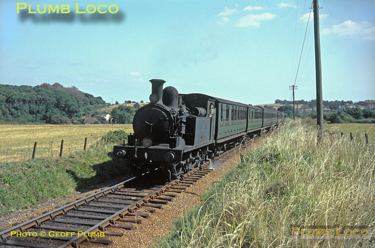 "O2 0-4-4T No. W21 ""Sandown"" is hard at work with a nice clean fire as it climbs the bank from Shanklin near Upper Hyde, en route to Wroxall and Ventnor with the 12:08 limited stop train from Ryde Pier Head. Saturday 29th August 1964. Slide No. 1009."