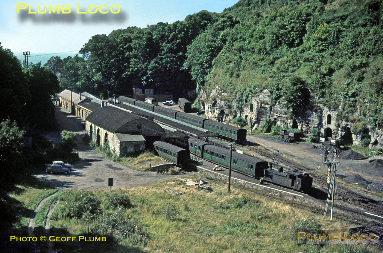 """The classic view of Ventnor station from St. Boniface Down as O2 0-4-4T No. W17 """"Seaview"""" awaits departure time for the 11:40 train to Ryde Pier Head - the signal is """"off"""" but the fireman is still trimming coal in the bunker. Note the spare coaches in the sidings and the coal wagons being unloaded by the coal merchants based in the caves in the hillside. Sunday 30th August 1964. Slide No. 1021."""