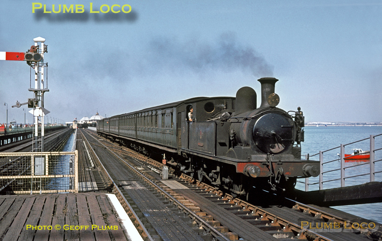 """O2 Class 0-4-4T No. W24 """"Calbourne"""" drifts into Ryde Esplanade station at the landward end of Ryde Pier, having just left Pier Head with the 14:28 train to Ventnor on a glorious sunny day, Sunday 30th August 1964. This engine is the sole survivor of the class and has recently undergone another rebuild at the Isle of Wight Steam Railway based at Haven Street. The engines didn't carry the """"W"""" prefix to their numbers, except on a small numberplate on the rear of the bunker! Slide No. 990."""