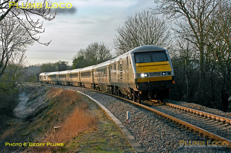 """Another frosty morning, but at last some sunshine as well! 82304 leads 1R14, the 08:37 from Marylebone to Birmingham Moor Street, with 67013 """"Dyfrbont Pontcysyllte"""" bringing up the rear of the Chiltern Mainline Silver train. It is about to pass the foot-crossing south of Princes Risborough on the descent from Saunderton summit, where the up and down lines are grade separated. 09:05, Tuesday 17th January 2012. Digital Image No. GMPI10826."""