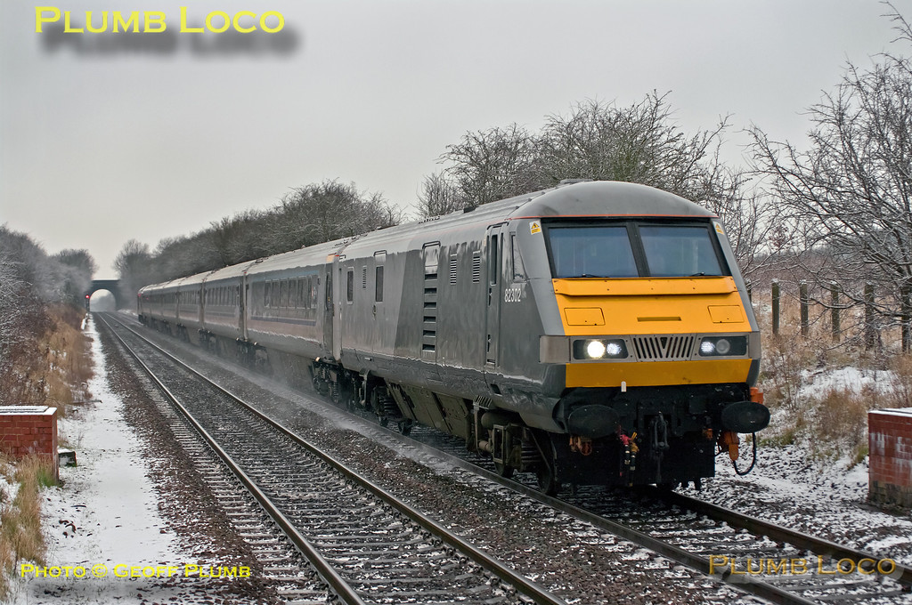 """As well as other changes to LHCS workings on Monday 14th January 2013, 1H22, the 06:38 from Stourbridge Junction to Marylebone was cancelled, apparently due to a points failure. However, 1H31, the 07:30 from Kidderminster was loco-hauled vice 168 unit, though it started from Stourbridge Junction and was delayed by some 24 minutes, due to the same points failure. Further time was lost en route and it was 39 minutes late passing Haddenham & Thame Parkway,where 82302 is seen leading 67015 """"David J. Lloyd"""" at 10:02. Digital Image No. GMPI13706."""