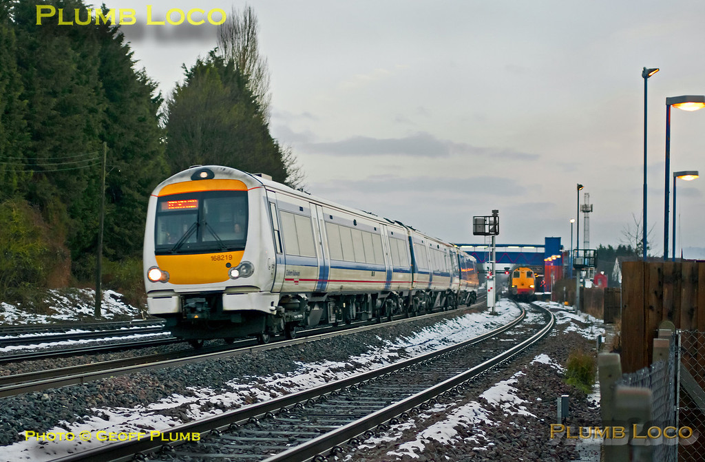 "168 219 speeds southwards through Princes Risborough on the up main line as it overtakes 20308 and 20312 in the platform. The 168 is working 1H04, the 06:42 from Birmingham Moor Street to Marylebone, running on time at 07:59, while the Class 20s are on 1Z20, the 05:05 Crewe to Liverpool Street ""Buffer Puffer"" railtour. Saturday 26th January 2013. Digital Image No. GMPI13803."