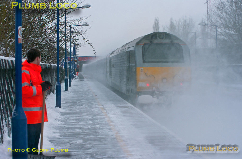 """Staff clearing snow at Haddenham & Thame Parkway station look on in bemusement as much of the snow they've cleared off the platform gets blown back on again as 1H53, the 12:55 from Birmingham Moor Street to Marylebone, passes with 82302 leading and 67015 """"David J. Lloyd"""" on the rear. 14:26, Friday 18th January 2013. Digital Image No. GMPI13782."""