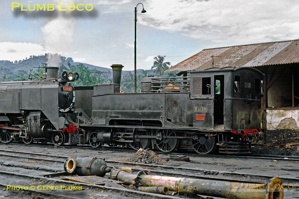 2-6-0T No. C11 39 (Hartmann No. 1721 of 1891) stands nose to nose with 4-6-4T No. C28 20 at Bandjar depot. The C28 is at least in steam, though whether likely to do anything was uncertain. The C11 looks serviceable, but again, quite what its duties might entail was an unknown detail. That steam was in decline even in these parts is perhaps illustrated by the state of the water column in the foreground, now demolished. Friday 20th July 1973. Slide No. 11375.