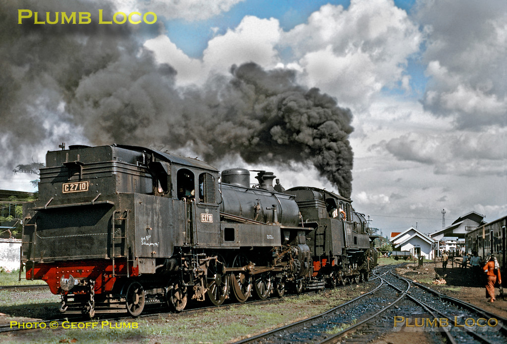 4-6-4WT No. C27 35 billows a cloud of oily smoke over the environs of Tanahabang as it shunts classmate C27 10 around the yard at the depot, the imposing station allover roof in the background. Tuesday 17th July 1973. There were 39 Class C27 from SLM, Werkspoor and Armstrong Whitworth from 1916-1922. C27 10 built by SLM in 1916, C27 35 by Armstrong Whitworth in 1922. Slide No. 11152.