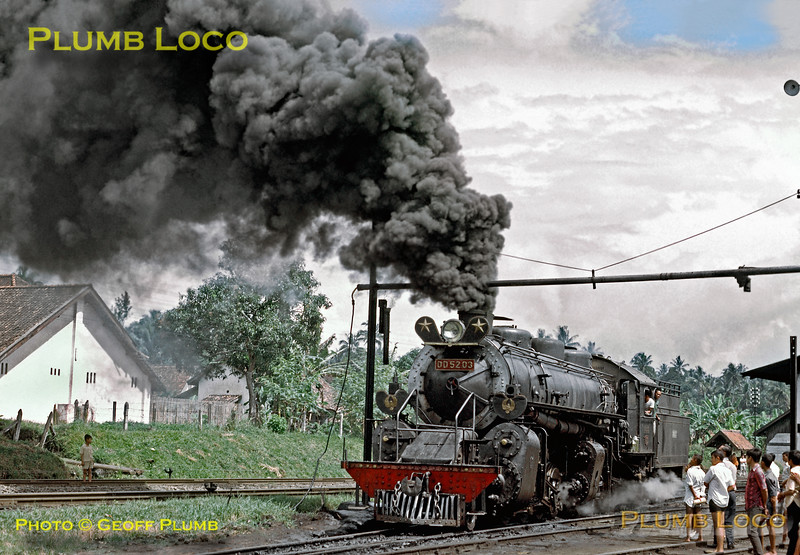 DD52 class 2-8-8-0 Mallet No. DD52 03 seemed to be the only serviceable engine of its class and is here being prepared to take a train along the main line from Tjibatu to Tasikmalaja. Watched by some of the local population, the engine casts a cloud of oily smoke over the surroundings before eventually moving off shed. Thursday 19th July 1973. Slide No. 11276.