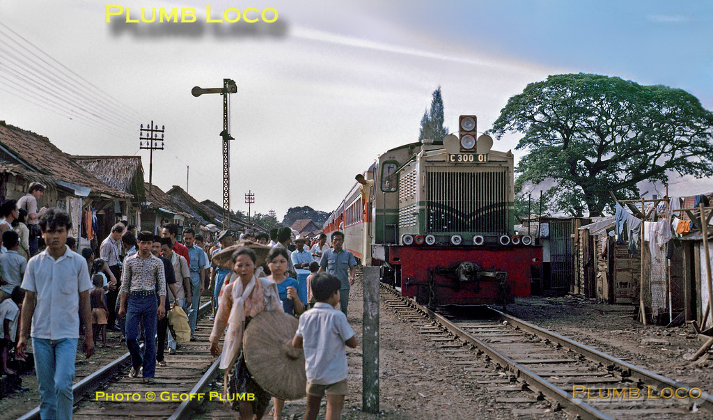 PNKA C300 Class 0-6-0D No. C300 01 (270hp, one of twenty built by Karl Marx, Works Number 263002-021 in 1966) threads its way through the crowds thronging the tracks as it approaches Tanahabang station with a passenger train from Djakarta Kota. The railway was used as a general thoroughfare, with people just wandering around as well as living, working and conducting their businesses on the tracks. When a train came along they just upped sticks for a while and then returned after its passing! Tuesday 17th July 1973. Slide No. 11171.