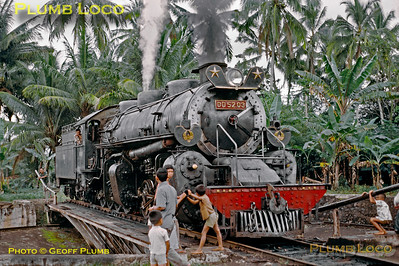 One of the massive PNKA 2-8-8-0 Mallets of class DD52, No. DD52 03 on the turntable at Tjibatu shed, where local kids are helping the shed staff turn the engine. It was being prepared to work a mixed train from Tjibatu to Tasikmalaya a while later. The loco was built by Hanomag in 1923, Works No. 10223. Thursday 19th July 1973. Slide No. 11256.