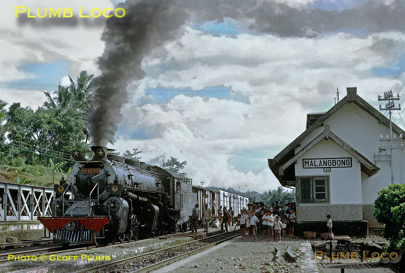 PNKA DD52 class 2-8-8-0 Mallet No. DD52 03 is en route from Tjibatu toTasikmalaja with a short freight train - though there are plenty of passengers on board. The train has just arrived in the station at Malangbong, to be met by a crowd of people, now unloading or loading their goods. Thursday 19th July 1973. DD52 03 was built by Hanomag in 1923, works No. 10223. Slide No. 11301.