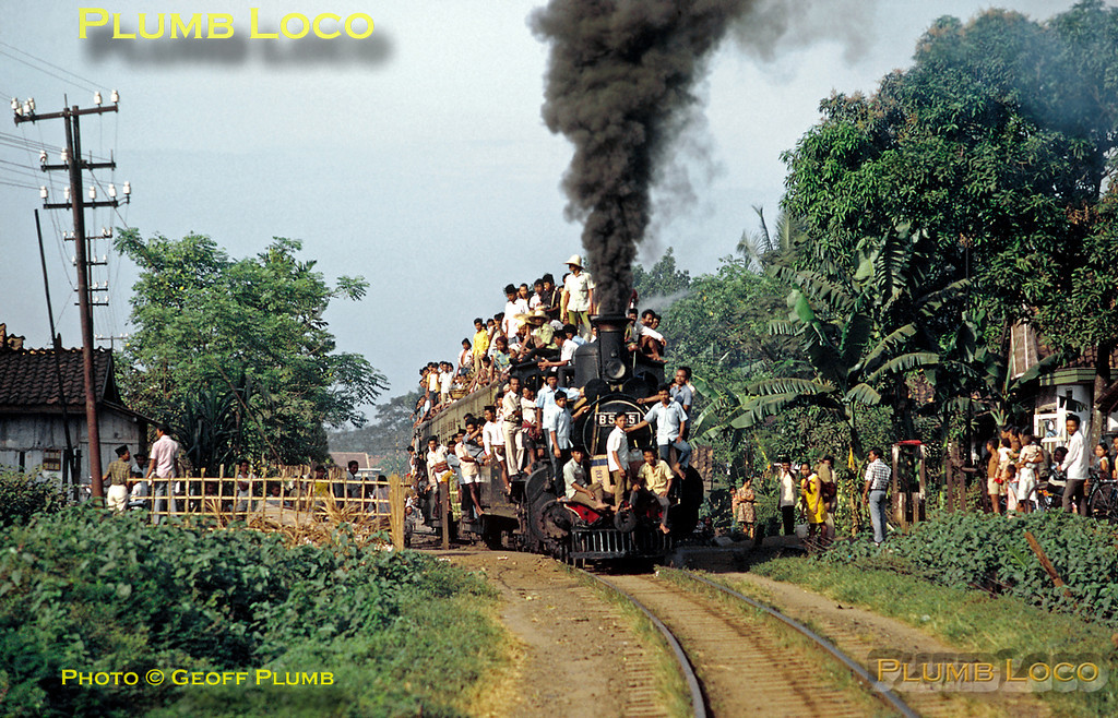 PNKA 4-4-0 No. B51 05 is in charge of the 07:18 train from Rangkasbetung to Tanahabang - its two coach train rather overloaded! It is departing from Kebajoran station at 08:30 on Friday 3rd August 1973 with rather a lot of passengers and their baggage - quite how they got on the roof with all their stuff is something of a mystery! B51 05 was built by Hanomag in 1900, works No. 3362. Slide No. 12302.