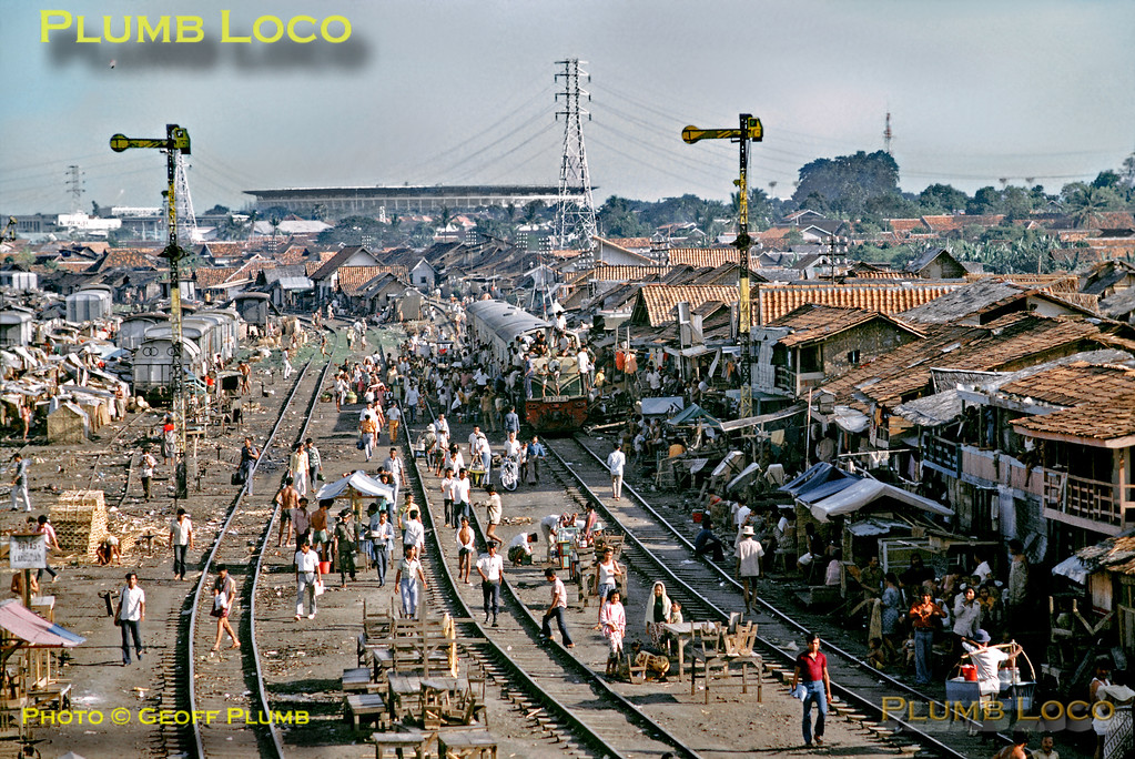 "In a scene almost incomprehensible in today's climate of Health & Safety awareness, life goes on in the yards at Tanahabang station, just south of Djakarta. Almost lost in the sea of people, a train from Rangkasbetung is arriving behind B-B diesel No. BB300 16 (30 engines built by Krupp in 1958/59, works numbers 3727-3756) and has stopped in the yard. All the tracks see some use, but there is a sort of ""tent-city"" over the tracks on the left, while market stalls are set up elsewhere between the tracks, other people literally living on top of the railway! The skyline is dominated by a new sports stadium built for the Asian Games. Tuesday 17th July 1973. Slide No. 11174."