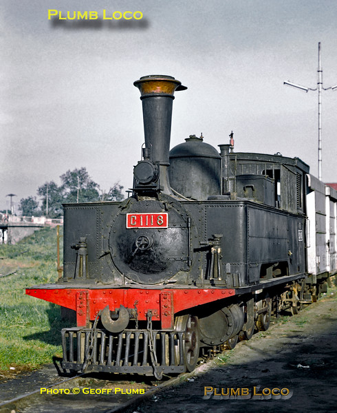 """2-6-0T No. C11 18 is a member of a class built by Hartmann between 1879 and 1891, No. 1429 of 1886, one of the oldest surviving classes in Java. Here she reposes in the early morning sun at Bandung shed. She is not in steam but the polished wheels suggest she has been running recently. Note the """"cage"""" on top of the firebox for storing firewood - though there is none on board. Thursday 19th July 1973. Slide No. 11223."""
