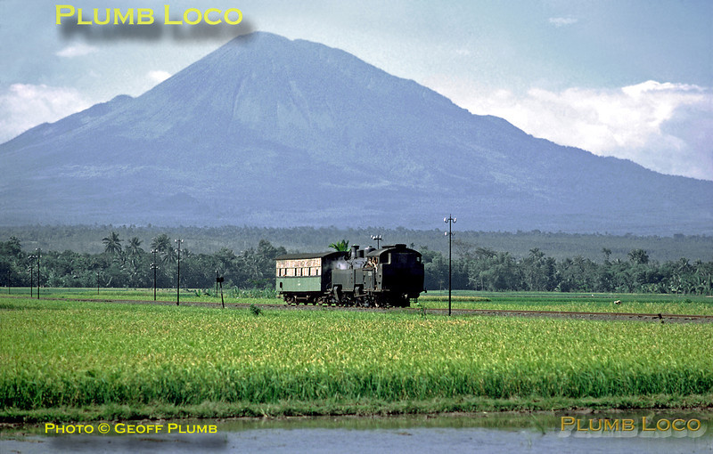 PNKA Mallet 2-6-6-0T No. CC10 03 trundles along south of Klakah with its one coach train on the branch line from Klakah to Lumadjang and Pasirian, near the southern coast of East Java. This was the 13:25 from Klakah, seen amongst the paddy fields near Sukodono. The loco was built by Hartmann in 1904, works No. 2859. Thursday 26th July 1973. In the background is a classic stratovolcano, Mount Lamongan, whose highest point is known as Gunung Tarub, 5,417 feet above sea level (1,651 metres). Slide No. 11898A.