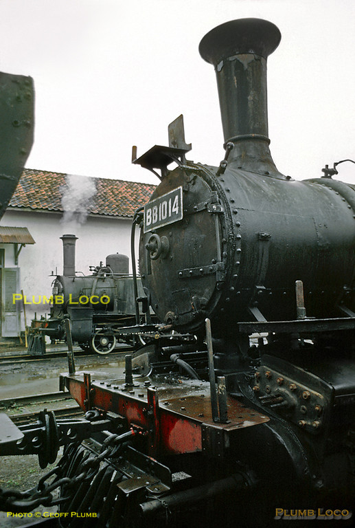 In the foreground is rain-soaked Mallet 0-4-4-2T No. BB10 14, dumped out of use at Tasikmalaja shed. In the background and in light steam is 2-4-0T No. B13 03, though quite what this loco was likely to do was uncertain. This was one of eleven locos built by Hanomag in 1885, Works No. 1857. Friday 20th July 1973. Slide No. 11350.