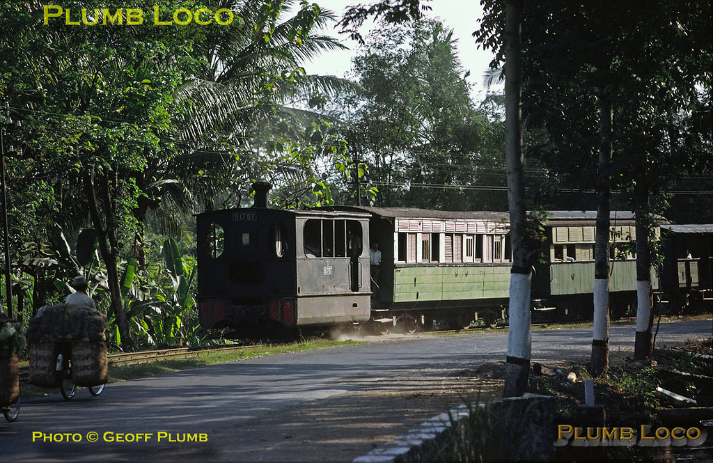 0-4-0Tr Tram Engine No. B17 07 is working the 14:02 mixed train from Kediri to Pare in East Java, along another roadside tramway, as a couple of local people on their well-laden bicycles pedal in the opposite direction. Exact location not known. B17 07 was one of a class of eleven locos built in batches by Hohenzollern from 1897 to 1905, this one in 1897, Works No. 1051. Sunday 29th July 1973. Slide No. 12119.