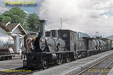 This was my first sight of one of the incredible B50 class 2-4-0s and it is being prepared to work the 14:15 train from Madiun to Ponorogo and Slahung, a branch line leading south from the main line at Madiun. This engine was an oil-burner, some others based here were wood-fired. The loco is having its boiler tubes cleared, smoke and flames appearing in all directions and as the engine is coupled to an auxiliary fuel tender and various oil wagons, with another oil tank wagon alongside, this was something of a worry! The engine was one of about seventeen built by Sharp Stewart from 1880 to 1885, B50 11 in 1883, works No. 3107. Tuesday 24th July 1973. Slide No. 11738.