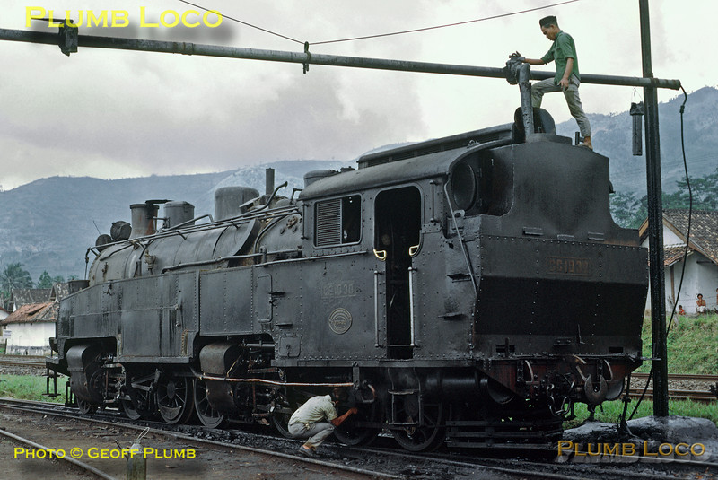 PNKA Class CC10 Mallet 2-6-6-0T No. CC10 30 arrived into Tjibatu with the morning train from the Tjikadjang branch and as the only serviceable engine for the return working it is being prepared in the yard at Tjibatu shed. The fireman is replenishing the oil bunker from the overhead delivery pipe whilst the driver oils round the motion. The loco was built by Werkspoor in Amsterdam, works number 256 of 1911. Thursday 19th July 1973. Slide No. 11284.