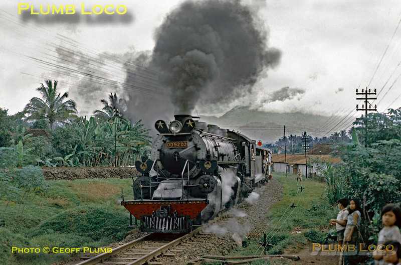 2-8-8-0 Mallet No. DD52 03 finally starts away from Tjibatu with its minimal freight train bound for Tasikmalaja on Thursday 19th July 1973. The line at a higher level to the left is the branch to Garut and Tjikadjang, taken by CC10 30 a few minutes earlier. This is train 348, booked to depart from Tjibatu at 12:15, but running rather late. Slide No. 11293.