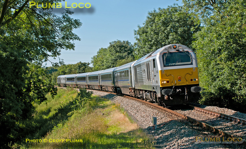 "Chiltern's second set of power door coaches is headed by 67012 ""A Shropshire Lad"" and DVT 82302 brings up the rear as 1R14, the 08:37 from Marylebone to Birmingham Moor Street, approaches the foot-crossing just south of Princes Risborough station at 09:06 on Monday 23rd July 2012. At this point the up and down lines are grade separated over Saunderton bank. Digital Image No. GMPI12314."