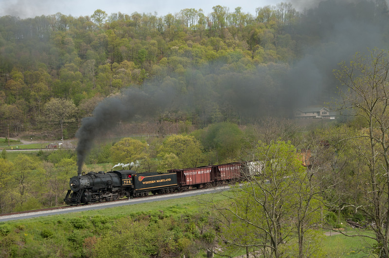The Western Maryland Scenic Railroad operates over the former Western Maryland main line, and for many years has featured stalwart 2-8-0 734, originally from Michigan but remodeled into a very credible replica of a WM steamer.  The 734 has recently gone out of service pending a thorough and much-needed rebuild.  Her place will be taken next year by the newly operable C&O 2-6-6-2 1309, now in the final stages of her return from static museum piece to living machine.<br /> <br /> Here the 734 storms upgrade around the landmark horseshoe curve above Cumberland, nicknamed Helmstetter in honor of the farmer's homestead it encircles.<br /> <br /> April 2011.