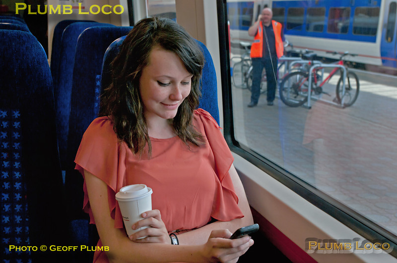 Emily, on work experience with Chiltern's PR department, enjoys a coffee as she tries out the seats aboard 172 102 during the official launch at Marylebone station, 15th July 2011. Digital Image No. GMPI9743.