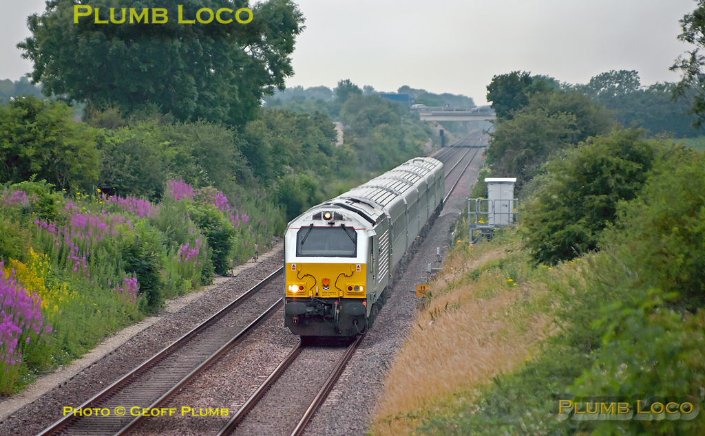 """Recent work on the roadbridge over the railway at Bucknell has opened up the view for a while, before the vegetation takes over again! 67013 """"Dyfrbont Pontcysyllte"""" is at full speed at it heads towards the stop at Bicester North with 1H06, the 05:43 from Birmingham Moor Street to Marylebone. 06:46, Monday 4th July 2011. Digital Image No. GMPI9574."""