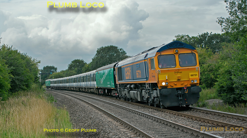 This was something of an elusive train! GBRf 66731 is at the head of 5O08, 10:00 from Donnington, near Telford, to Eastleigh, dragging two 508 units which had been in store at Donnington. The train was supposed to run on Tuesday 19th July, but due to problems with the 508 units concerned was initially postponed until later that day, then caped. The train was then rescheduled for the Thursday with two different 508s and departed on time from Donnington, but soon ran into trouble, being reported 148 minutes late only some ten miles or so into the journey. Further time was lost due to a track circuit failure after the train got on the move again and by the time it was seen here at Wormleighton crossing at 15:55 it was some 170 minutes late... It does make a colourful sight with its translator vans on a day of mixed dullness, showers and the odd sunny interval. Thursday 21st July 2011. Digital Image No. GMPI9829.