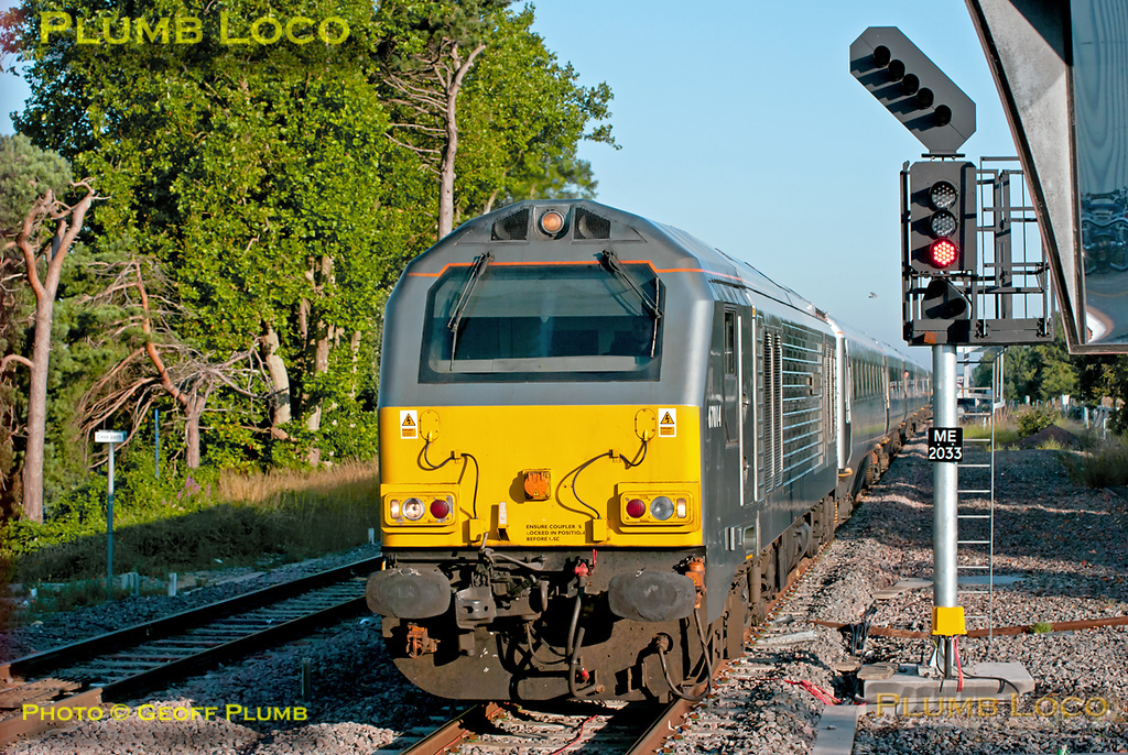 """67014 """"Thomas Telford"""" approaches the station stop at Bicester North with 1H06, the 05:43 from Birmingham Moor Street to Marylebone, due to depart here at 06:53 on a lovely sunny morning. Signals, signs, mirrors and shadows make this rather a restricted spot for photos though! 06:50, Monday 11th July 2011. Digital Image No. GMPI9668."""