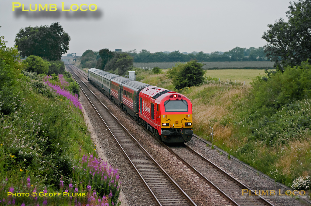 """67018 """"Keith Heller"""" returns from Banbury on a dull Monday morning, 4th July 2011. It is working 1H08, the 06:53 from Banbury to Marylebone with the Chiltern """"Hybrid"""" set AL02. With the M40 bridge in the background it is passing Bucknell at 07:03, the view at this location having been opened up by recent bridge reconstruction work. Digital Image No. GMPI9582."""