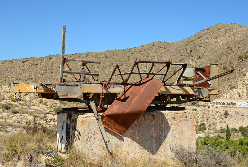The remains of an Alicante trailer car as seen at Barranco De Aguas near El Campello 30/06/2014. My understanding is that this was used to publicise a local restaurant. In the background can be seen the Tram line covered in grafiiti, a major problem in Spain.
