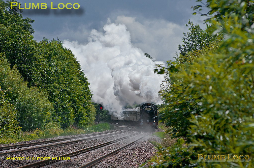 "The heavens had opened a short while before and it absolutely poured, but fortunately, the sun came out again a couple of minutes prior to 5043 ""Earl of Mount Edgcumbe"" coming into view, and what a sight! The engine is going all out as it gets to grips after the water stop at Newbury Racecourse, here seen approaching a foot-crossing just west of Kintbury. The train is 1Z50, ""The Collett Express"", though it is carrying ""The Bristolian"" headboard. It departed from Solihull at 07:05 and is bound for Bristol at 12:00 on Saturday 18th June 2011. The strange effect in front of the train is steam coming off the track as the sun dries up the rain! Digital Image No. GMPI9452."