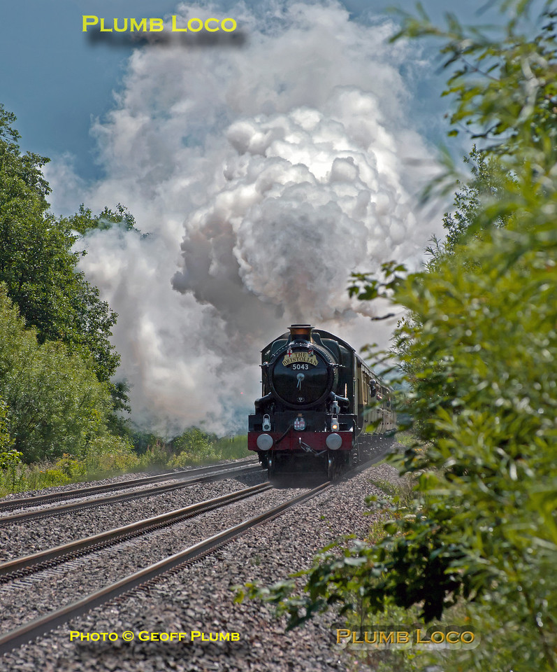 "The heavens had opened a short while before and it absolutely poured, but fortunately, the sun came out again a couple of minutes prior to 5043 ""Earl of Mount Edgcumbe"" coming into view, and what a sight! The engine is going all out as it gets to grips after the water stop at Newbury Racecourse, here seen approaching a foot-crossing just west of Kintbury. The train is 1Z50, ""The Collett Express"", though it is carrying ""The Bristolian"" headboard. It departed from Solihull at 07:05 and is bound for Bristol at 12:00 on Saturday 18th June 2011. Digital Image No. GMPI9453."